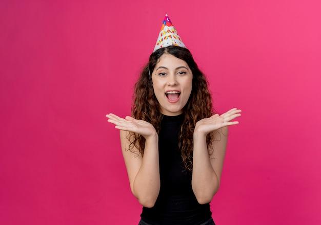 ピンクの壁の上に立っているホリデーキャップの巻き毛と驚きと幸せな誕生日パーティーのコンセプトの若い美しい女性