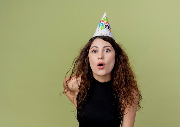 明るい壁の上に立っている休日の帽子の巻き毛の若い美しい女性は誕生日パーティーのコンセプトを驚かせた