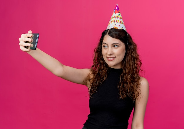 ピンクの壁の上に立っている陽気な誕生日パーティーのコンセプトを笑顔で自分撮りを取っているホリデーキャップの巻き毛の若い美しい女性
