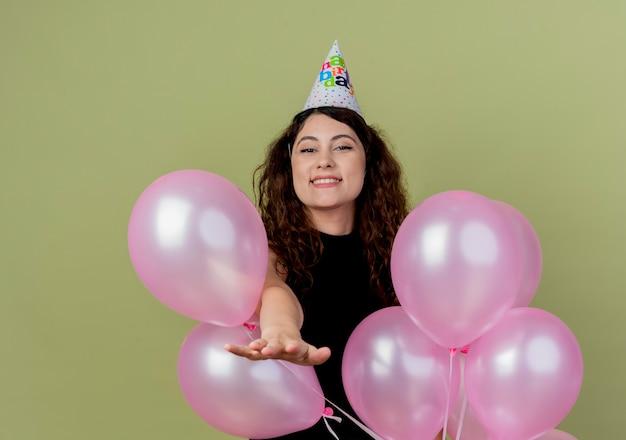 생일 파티를 축하하는 공기 풍선과 함께 휴가 모자에 곱슬 머리를 가진 젊은 아름 다운 여자 행복하고 긍정적 인 빛 벽 위에 유쾌하게 서 미소