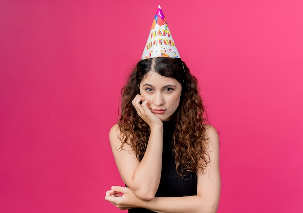 핑크 위에 슬픈 표정 생일 파티 개념으로 휴가 모자에 곱슬 머리를 가진 젊은 아름 다운 여자
