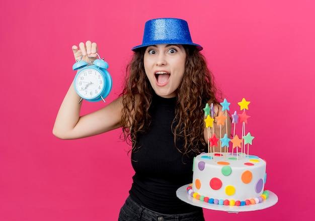 ピンクの壁の上に立っている驚きの誕生日パーティーのコンセプトを探している誕生日ケーキと目覚まし時計を保持している休日の帽子で巻き毛の若い美しい女性