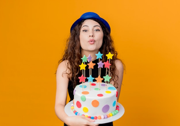 オレンジ色の壁の上に幸せで前向きに立ってキスを吹くバースデーケーキを保持している休日の帽子で巻き毛の若い美しい女性