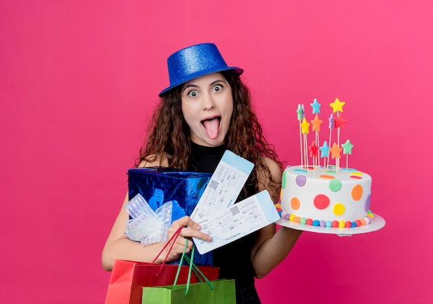 Молодая красивая женщина с вьющимися волосами в праздничной шляпе держит подарочную коробку для торта на день рождения и авиабилеты, сумасшедшая концепция вечеринки по случаю дня рождения над розовым
