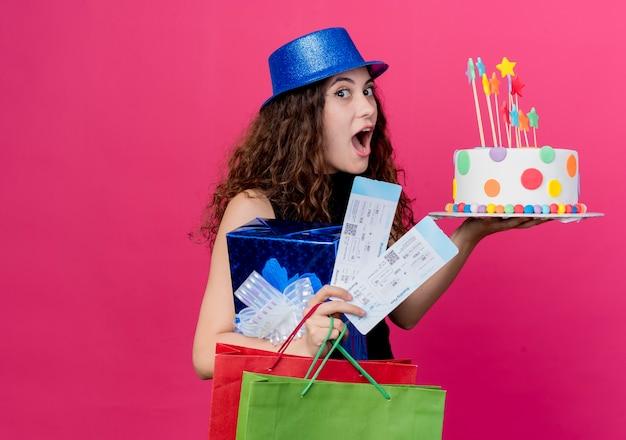 ピンクの壁の上に立っている誕生日ケーキのギフトボックスと航空券幸せで興奮した誕生日パーティーのコンセプトを保持している休日の帽子で巻き毛の若い美しい女性