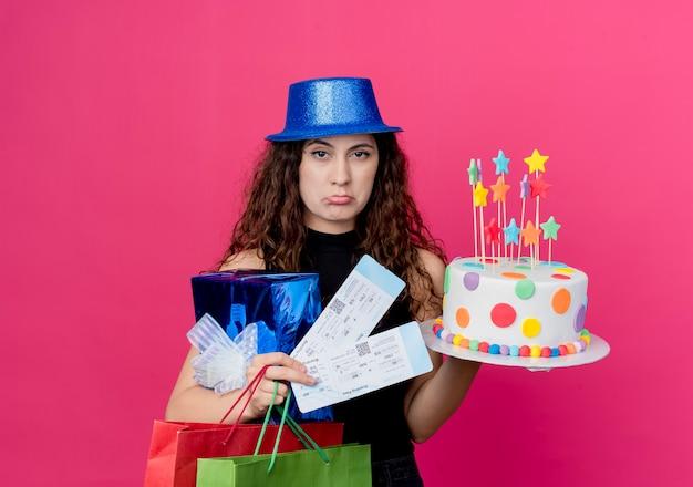핑크 벽 위에 서 슬픈 표정 생일 파티 개념으로 생일 케이크 선물 상자와 항공 티켓을 들고 휴가 모자에 곱슬 머리를 가진 젊은 아름 다운 여자