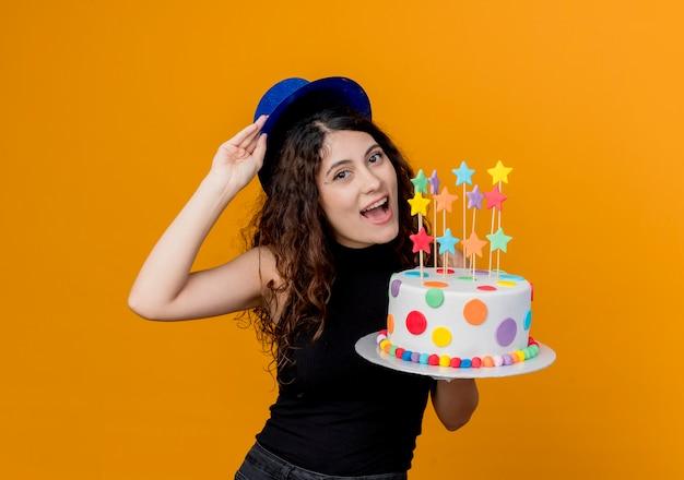 Молодая красивая женщина с вьющимися волосами в праздничной шляпе держит праздничный торт, счастливая и веселая стоя над оранжевой стеной