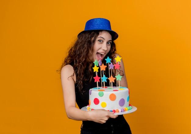 オレンジ色の壁の上に立って幸せで陽気なバースデーケーキを保持している休日の帽子の巻き毛の若い美しい女性