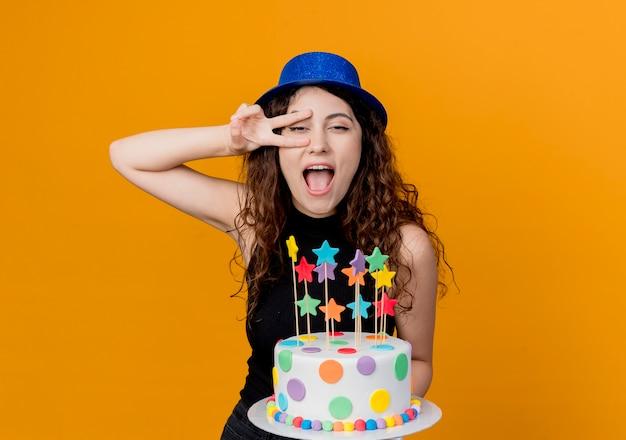 Молодая красивая женщина с вьющимися волосами в праздничной шляпе держит праздничный торт, счастливая и взволнованная, показывая v-знак, стоящий над оранжевой стеной