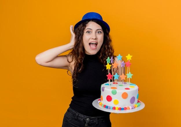オレンジ色の壁の上に立って幸せで驚きのバースデーケーキを保持している休日の帽子の巻き毛の若い美しい女性