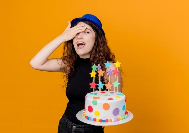 オレンジ色の壁の上に立って驚いて幸せそうに見えるバースデーケーキを保持している休日の帽子で巻き毛の若い美しい女性