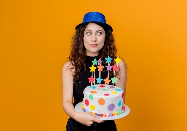 オレンジ色の壁の上に立っている顔に笑顔で脇を見てバースデーケーキを保持している休日の帽子で巻き毛の若い美しい女性