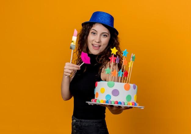 オレンジ色の壁の上に元気に幸せで前向きに立って笑顔のバースデーケーキを保持している休日の帽子で巻き毛の若い美しい女性