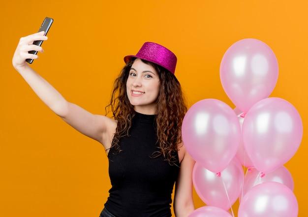 오렌지 벽 위에 유쾌하게 생일 파티 개념 서 웃고 셀카를하고 공기 풍선의 무리를 들고 휴가 모자에 곱슬 머리를 가진 젊은 아름 다운 여자