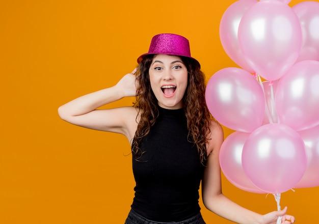 오렌지 벽 위에 서 공기 풍선 행복하고 흥분 생일 파티 개념의 무리를 들고 휴가 모자에 곱슬 머리를 가진 젊은 아름 다운 여자