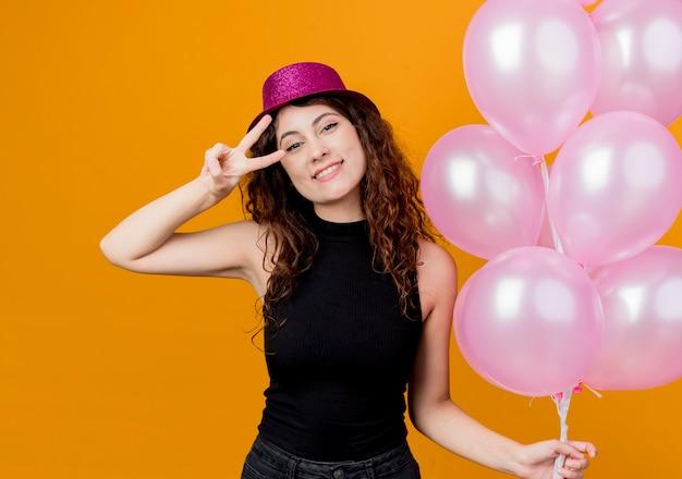 행복 하 고 긍정적 인 오렌지 벽 위에 서있는 v 기호 생일 파티 개념을 보여주는 유쾌 하 게 웃는 공기 풍선의 무리를 들고 휴가 모자에 곱슬 머리를 가진 젊은 아름 다운 여자