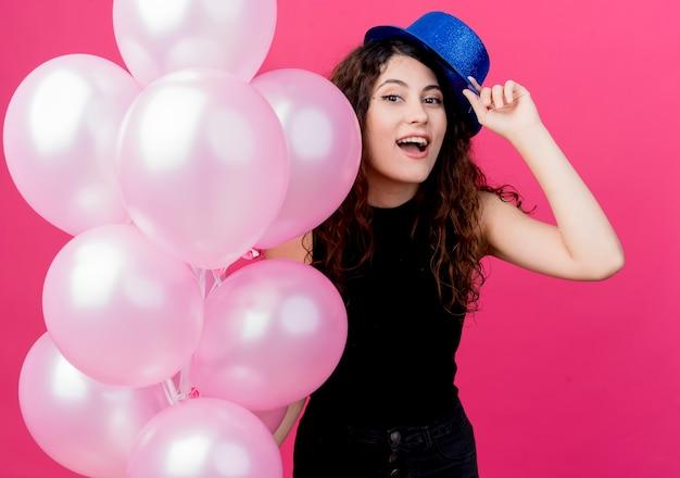 분홍색 위에 유쾌하게 웃는 공기 풍선 잔뜩 들고 휴가 모자에 곱슬 머리를 가진 젊은 아름 다운 여자