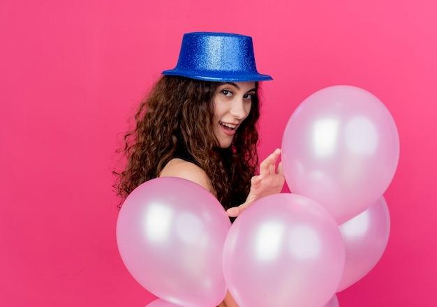 분홍색 벽에 행복하고 긍정적 인 서 미소 공기 풍선의 무리를 들고 휴가 모자에 곱슬 머리를 가진 젊은 아름 다운 여자