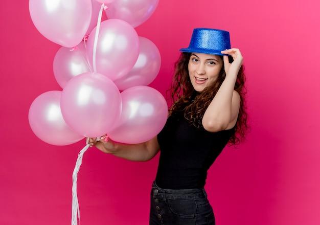 분홍색 벽 위에 서 웃 고 공기 풍선의 무리를 들고 휴가 모자에 곱슬 머리를 가진 젊은 아름 다운 여자