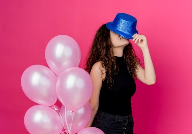 분홍색 벽 위에 서있는 공기 풍선의 무리를 들고 휴가 모자에 곱슬 머리를 가진 젊은 아름 다운 여자