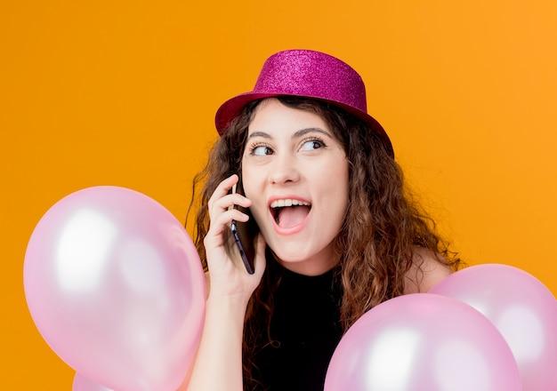 オレンジ色の壁の上に立っている携帯電話で幸せで興奮した誕生日パーティーのコンセプトを話している気球の束を保持している休日の帽子で巻き毛の若い美しい女性