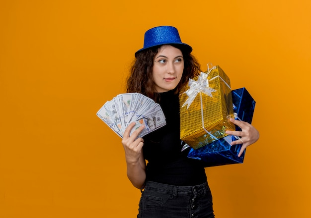 오렌지 벽 위에 canera 행복하고 쾌활한 서보고 현금과 선물을 들고 파티 모자에 곱슬 머리를 가진 젊은 아름 다운 여자
