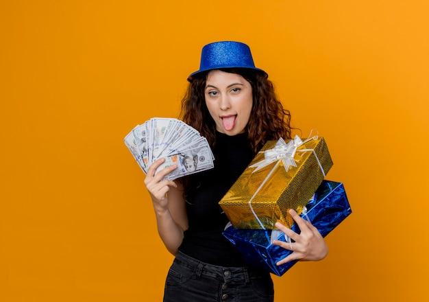 Молодая красивая женщина с вьющимися волосами в партийной шляпе держит деньги и подарки, глядя на счастливую и взволнованную канеру, высунув язык над апельсином