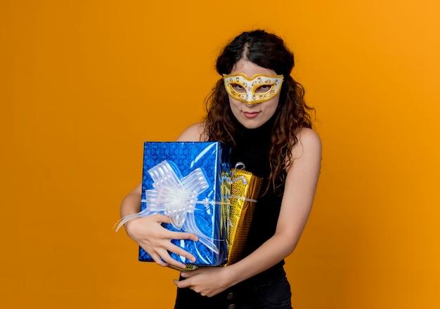 오렌지 벽 위에 서 웃는 선물을 들고 파티 마스크에 곱슬 머리를 가진 젊은 아름 다운 여자