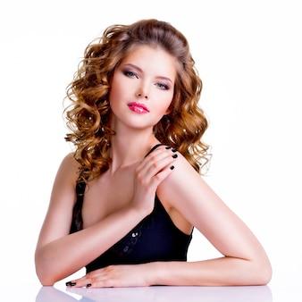 Giovane bella donna con i capelli ricci che guarda l'obbiettivo - isolata su bianco.