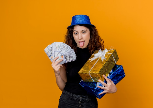 Young beautiful woman with curly hair in party hat holding cash and gifts looking at canera happy and excited sticking out tongue over orange