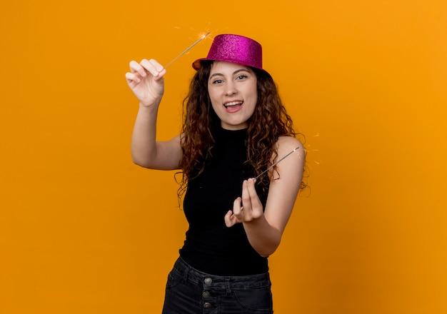Giovane bella donna con capelli ricci in cappello del partito che tiene le stelle filanti felici ed eccitate in piedi sopra la parete arancione