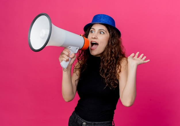 Giovane bella donna con capelli ricci in cappello del partito che grida al megafono essendo felice ed eccitato in piedi sopra la parete rosa