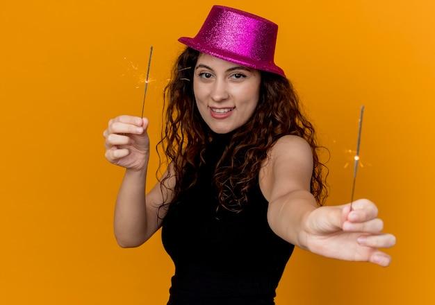 Giovane bella donna con capelli ricci in cappello del partito che mostra le stelle filanti sorridenti felici e allegri che stanno sopra la parete arancione