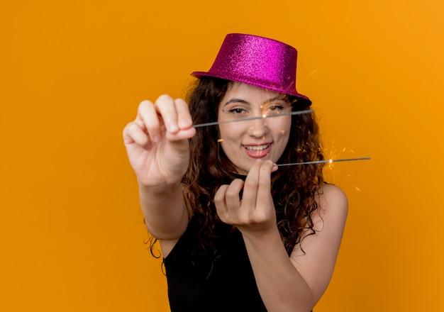 Giovane bella donna con capelli ricci in cappello del partito che mostra le stelle filanti felici e allegre in piedi sopra la parete arancione