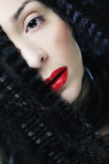 Young beautiful woman with curly hair and red lips