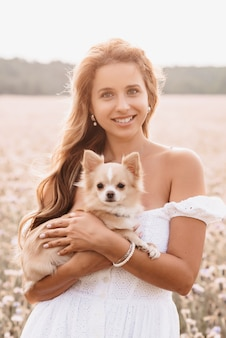 Young beautiful woman with cute chihuahua dog in nature in summer in a field of flowers