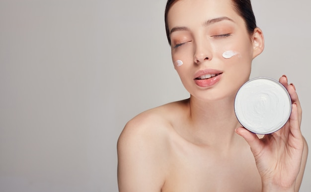 Young beautiful woman with dark hair and closed eyes holds face cream in her left hand. face cream woman beauty portrait.