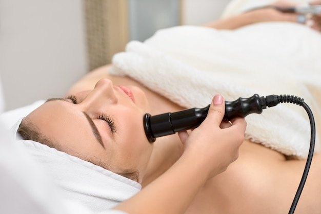 Young beautiful woman with dark hair gets procedure in the beauty salon.
