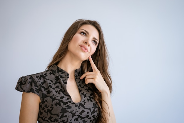 A young beautiful woman with dark hair holding a finger to her chin with a thoughtful look, against a white background in a black dress. concept of problem solving