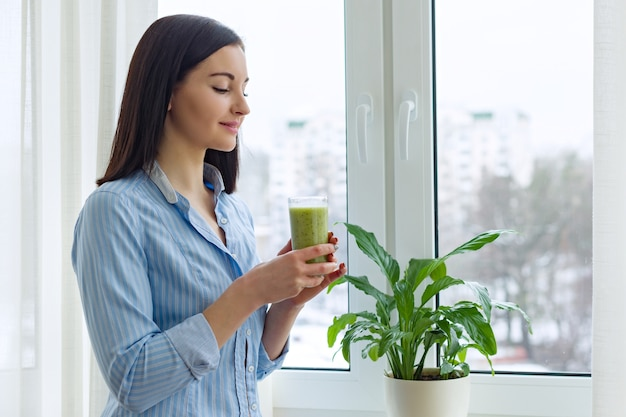 Young beautiful woman with diet vitamin drink green blended smoothie kiwi celery