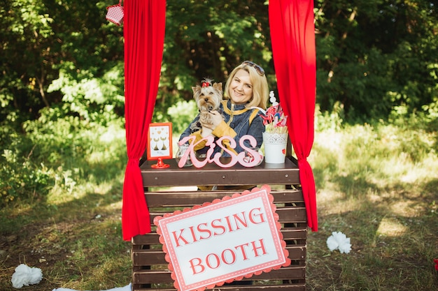 A young beautiful woman with a dog in the photo zone kissing booth in the forest on a holiday