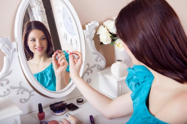 ドレスを着た若い美しい女性が化粧を適用します。美容とヘルスケアの概念。 。
