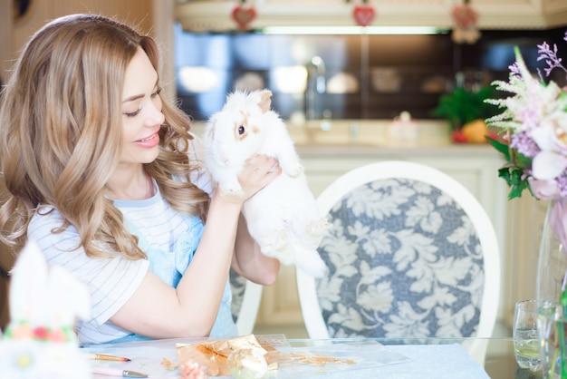 家でイースターバニーと若い美しい女性。