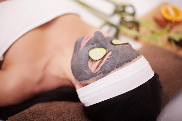 Молодая красивая женщина с лицевой маской из огурца на лице, лежа в спа-салоне