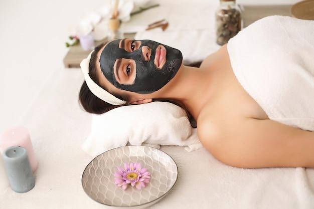 Молодая красивая женщина с маской для лица, спа-процедуры