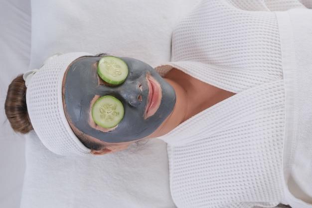 顔のマスクを持つ若い美しい女性