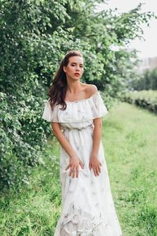 ファッションヘアスタイルと夏の庭でメイクの若い美しい女性