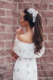 茶色のレンガの壁にファッションヘアスタイルを持つ若い美しい女性