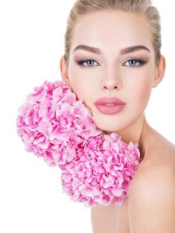 顔の近くに花を持つ若い美しい女性。