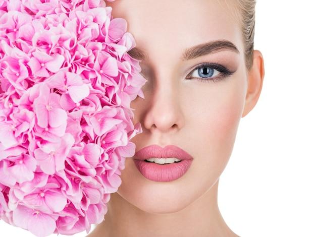 얼굴 가까이 꽃과 젊은 아름 다운 여자.